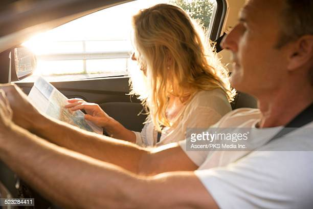 View through car of couple using map, driving