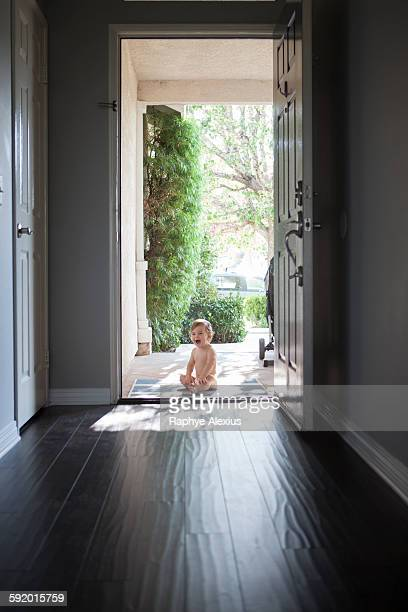 View through entrance hall of baby boy sitting outside at open front door, looking at camera open mouthed