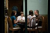 View through glass doors of family having dinner
