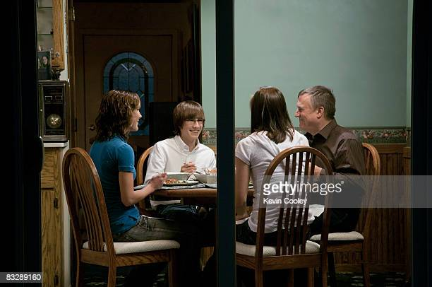 View through glass doors of family having dinner