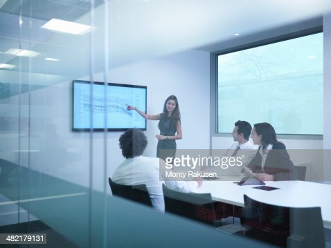 View through glass wall of business colleagues using screen in meeting