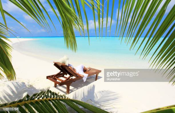 View through palm leaves at woman an deck chair.