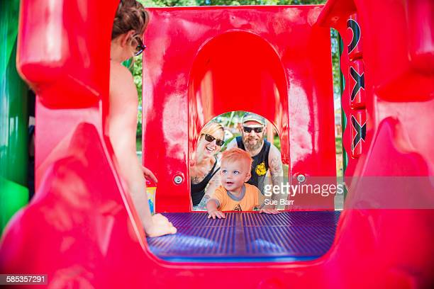 View through playground equipment of mother and father encouraging baby boy