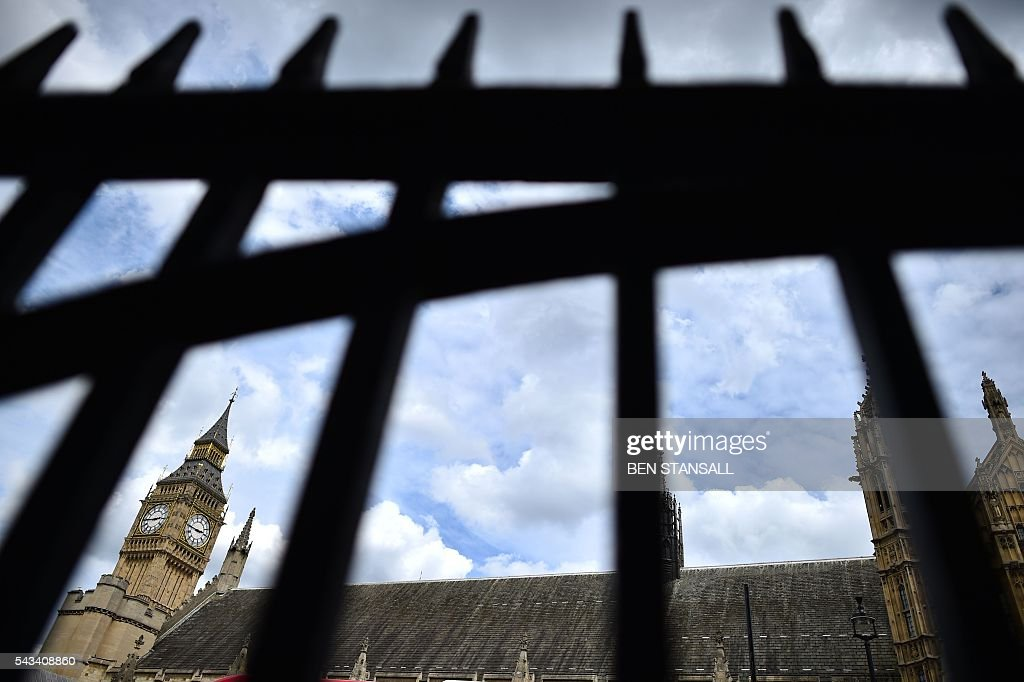A view through the fence to St Margaret's church roof and the Big Ben clock face on the Elizabeth Tower (R) in the Palace of Westminster in central London on June 28, 2016. EU leaders attempted to rescue the European project and Prime Minister David Cameron sought to calm fears over Britain's vote to leave the bloc as ratings agencies downgraded the country. Britain has been pitched into uncertainty by the June 23 referendum result, with Cameron announcing his resignation, the economy facing a string of shocks and Scotland making a fresh threat to break away. / AFP / BEN