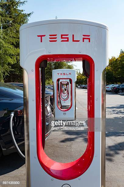 View through the hollow middles of several chargers with Tesla logos at a Supercharger rapid battery charging station for the electric vehicle...