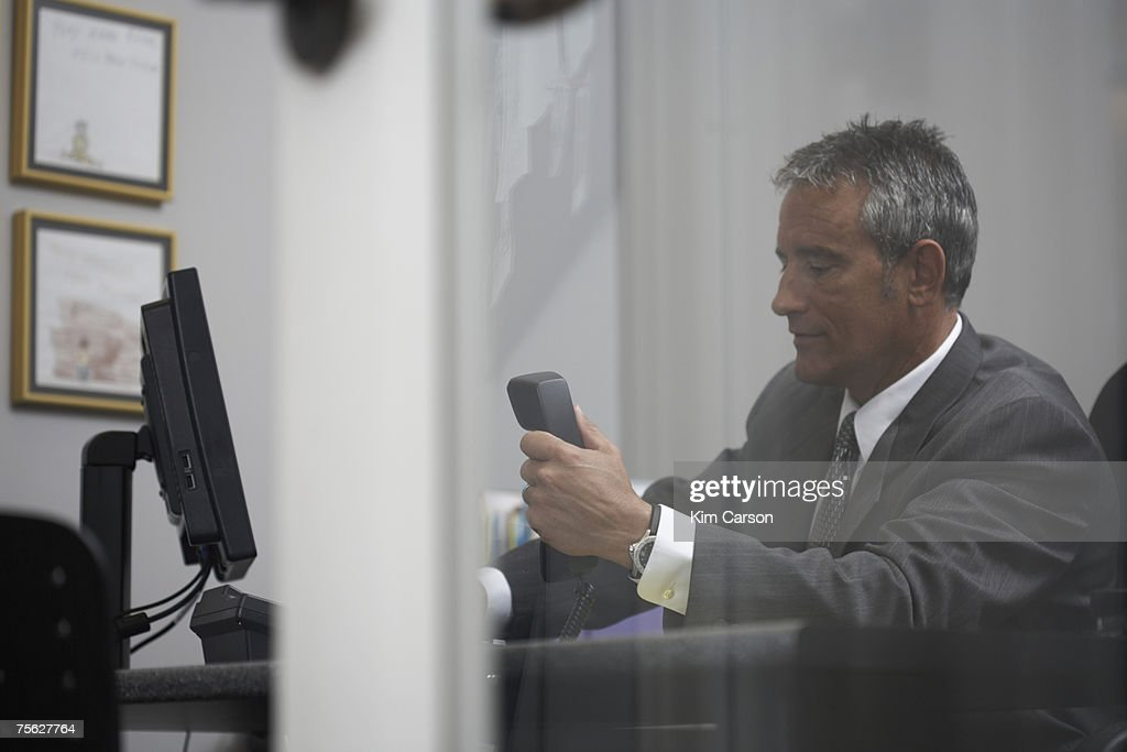View through window of businessman at desk in office : Stock Photo