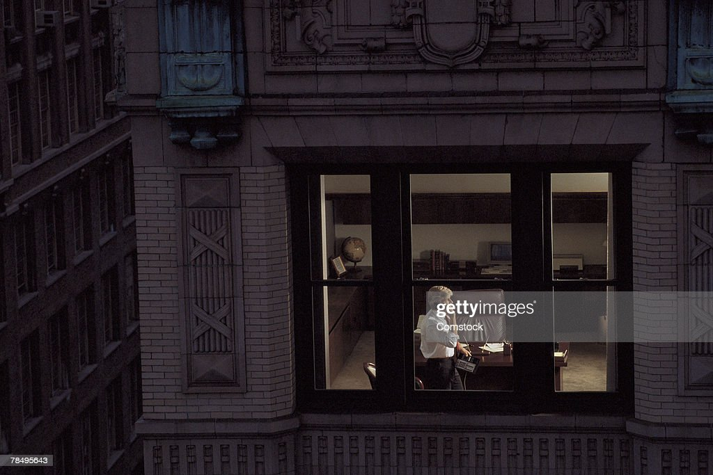 View through window of businessman on phone : Stock Photo