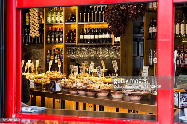 View through window of pintxos tapas on counter and shelves of wine bottles, Bilbao, Spain
