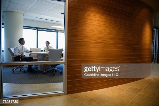 View through window to businesspeople working : Stock Photo