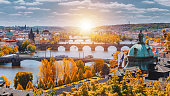 View to the historical bridges, Prague old town and Vltava river from popular view point in the Letna park (Letenske sady), beautiful autumn landscape in soft yellow light, Czech Republic