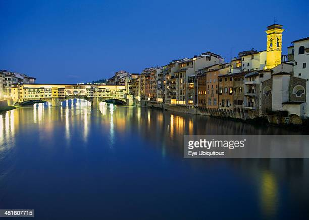 View towards the Ponte Vecchio and waterside buildings at night with lights reflected in the River Arno