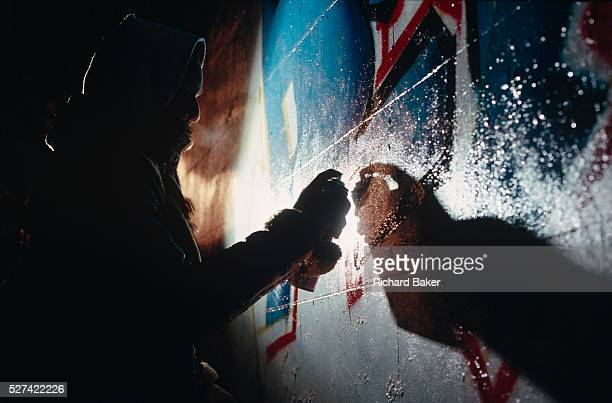 Viewed from a low angle an unidentified youth is seen spraying graffiti art on to a wall in the Notting Hill area of West London England We see his...
