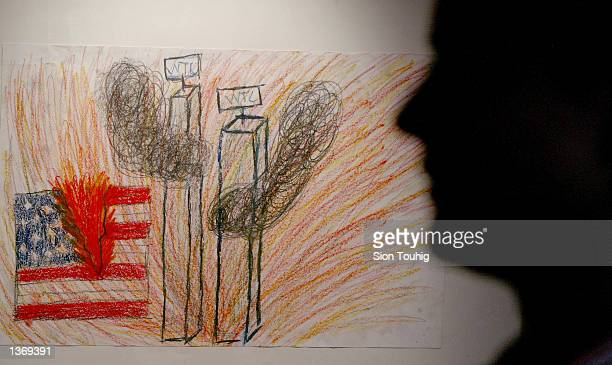 A viewer passes in front of a child's drawing portraying the terrorist attack on the World Trade Center September 5 2002 at an art exhibition of...