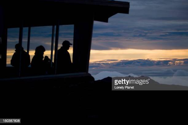 Viewing the dawn whilst keeping warm inside the summit building at Pu'u Ula'ula Overlook, Haleakala National Park.