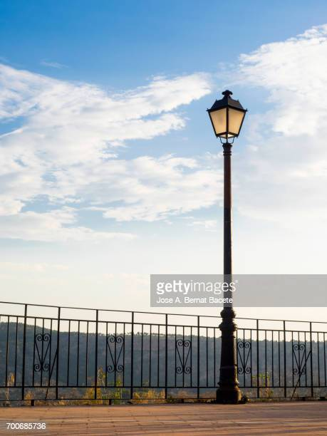 Viewing-point on a mountain with a rail of iron and a lamppost, illuminated by the light of the dawn