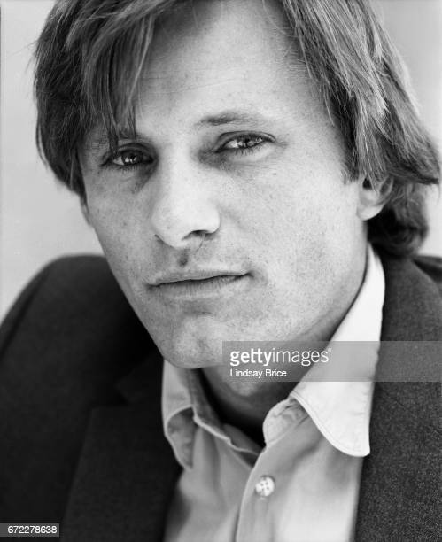 Viggo Mortensen dressed in a buttondown shirt and sport coat turns his face to his left toward the camera and looks directly into the lens during a...