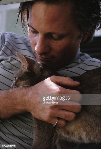 Viggo Mortensen holds Remy an Abyssinian cat close to his chest and smiles as he looks down to the cat during a photo session on April 13 1997 in...