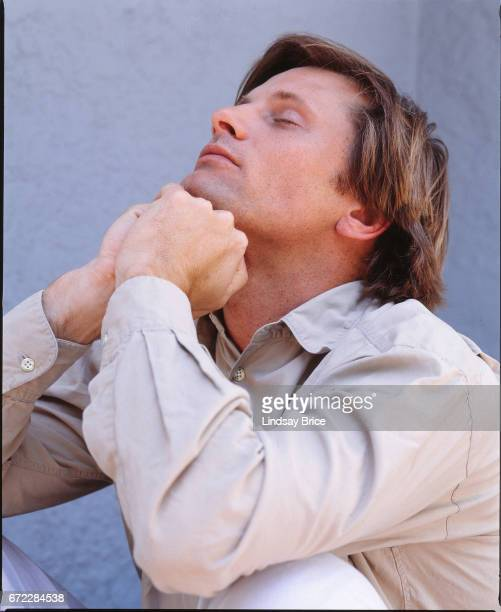 Viggo Mortensen in profile dressed in a tan buttondown shirt as he sits on a porch before a blue wall and tilts his head backward he supports his...