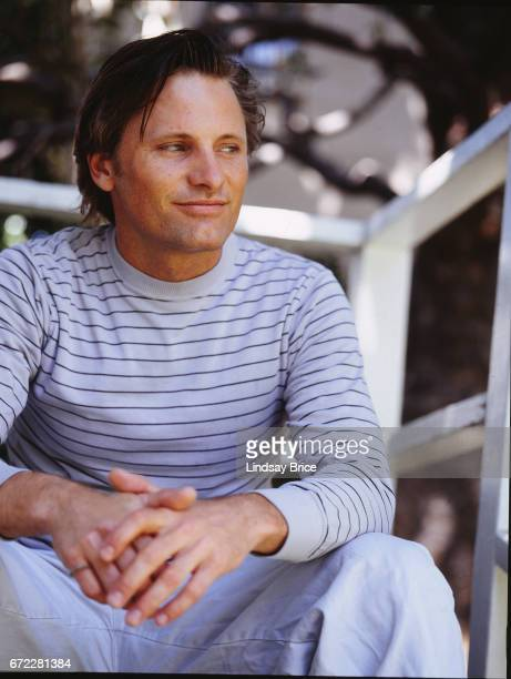 Viggo Mortensen wearing a light blue with navy pinstriped tee and white jeans smiles as he looks to his left and clasps his hands in his lap while...