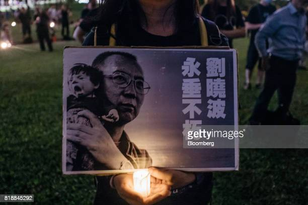 A vigil participant holds a photograph of Chinese Nobel Peace Prizewinner Liu Xiaobo during a memorial vigil in Hong Kong China on Wednesday July 19...
