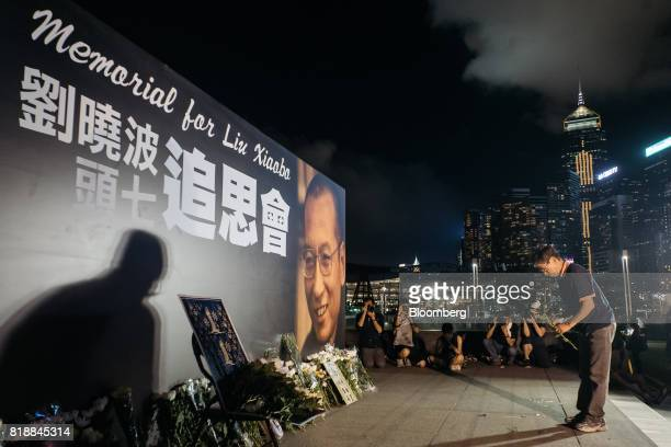 A vigil participant lays white flowers in front of a large portrait of Liu Xiaobo during a memorial vigil held for Chinese Nobel Peace Prizewinner...