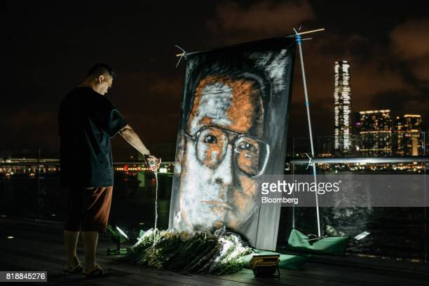 A vigil participant pours wine in front of a large portrait of Liu Xiaobo during a memorial vigil held for Chinese Nobel Peace Prizewinner Liu Xiaobo...