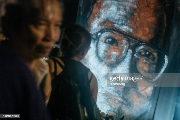 Vigil participants lay flowers in front of a large portrait of Liu Xiaobo during a memorial vigil held for Chinese Nobel Peace Prizewinner Liu Xiaobo...