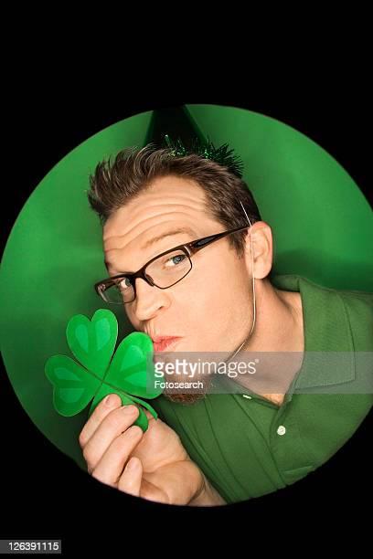 Vignette of adult Caucasian man on green background wearing Saint Patricks Day hat and kissing shamrock.