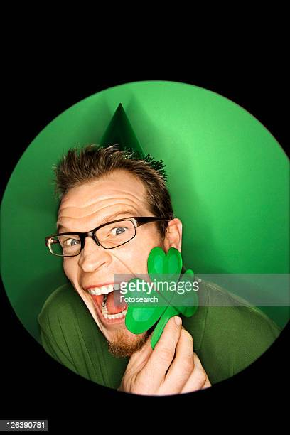 Vignette of excited adult Caucasian man on green background wearing Saint Patricks Day hat and holding shamrock.
