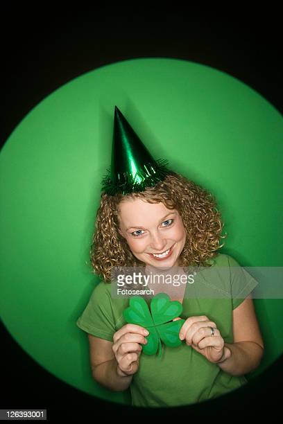 Vignette of smiling young adult Caucasian woman on green background wearing Saint Patricks Day hat and holding shamrock.