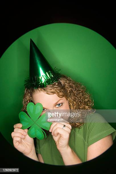 Vignette of young adult Caucasian woman on green background wearing Saint Patricks Day hat and holding shamrock.