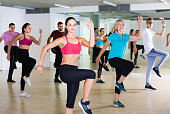 vigorous men and ladies dancing aerobics at lesson in the dance class