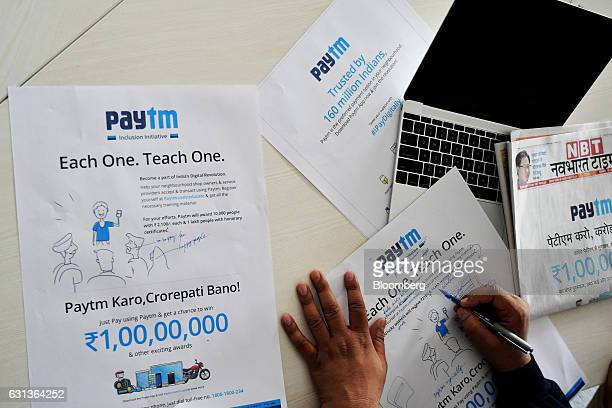 Vijay Shekhar Sharma founder and chairman of One97 Communications Ltd operator of PayTM make notes on a draft of a newspaper advertisement campaign...
