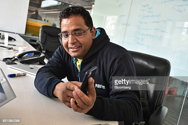 Vijay Shekhar Sharma founder and chairman of One97 Communications Ltd operator of PayTM shows his smartphone to colleagues unseen during a meeting at...