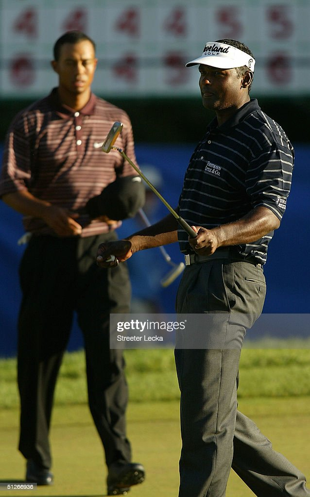 Vijay Singh of Fiji reacts to winning as Tiger Woods walks across the 18th green during the final round of the Deutsche Bank Championship on...