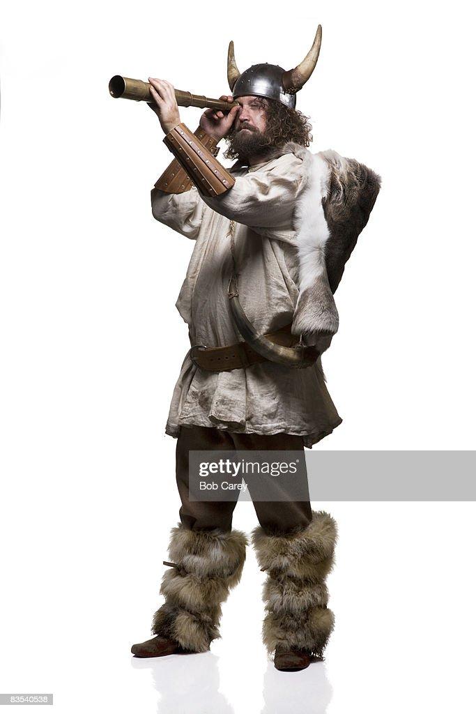 Viking looking through telescope on white.