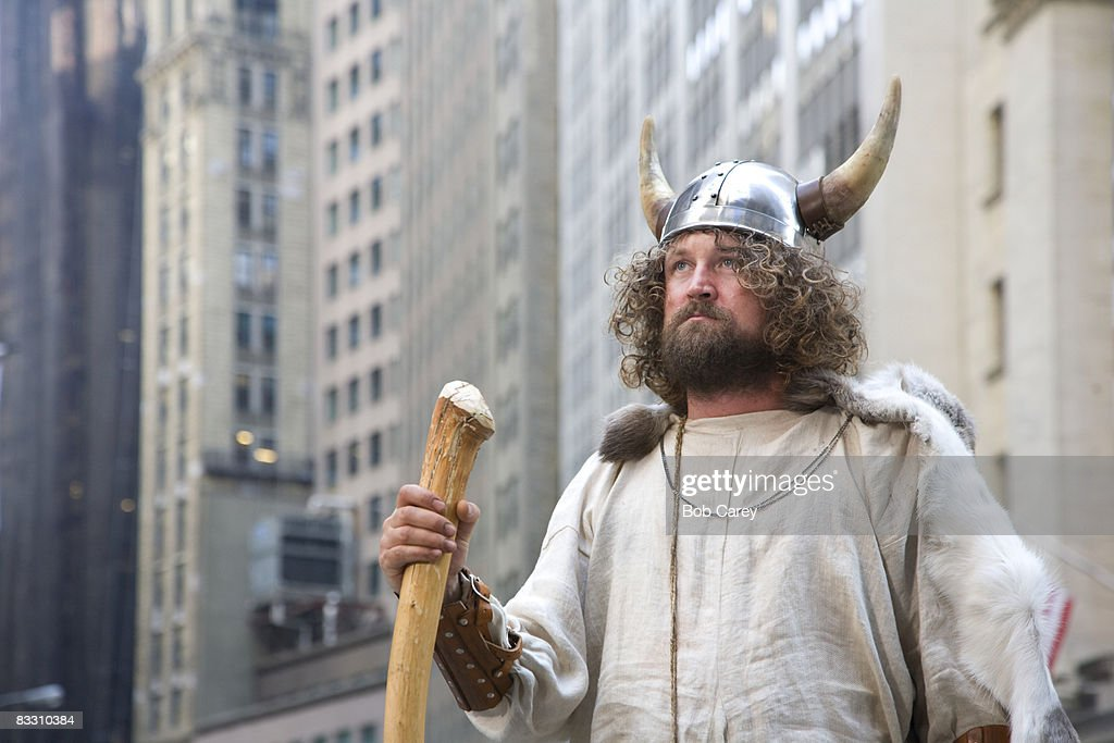 Viking looking up at tall buildings in the city.