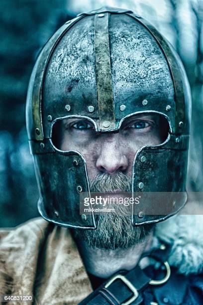 Viking warrior with beard wears helmet