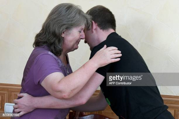 Viktor Ageyev a Russian detained in the wartorn Ukrainian east hugs his mother Svetlana Ageyeva as he is presented to the media during a meeting...