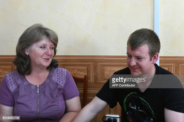 Viktor Ageyev a Russian detained in the wartorn Ukrainian east sits with his mother Svetlana Ageyeva as he is presented to the media during a meeting...