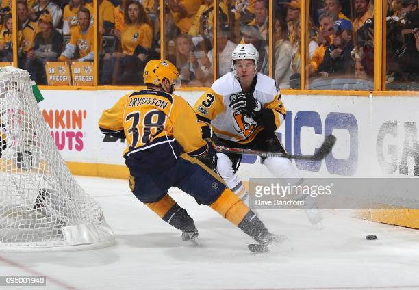Viktor Arvidsson of the Nashville Predators and Olli Maatta of the Pittsburgh Penguins skate behind the net for the puck in the third period of Game...