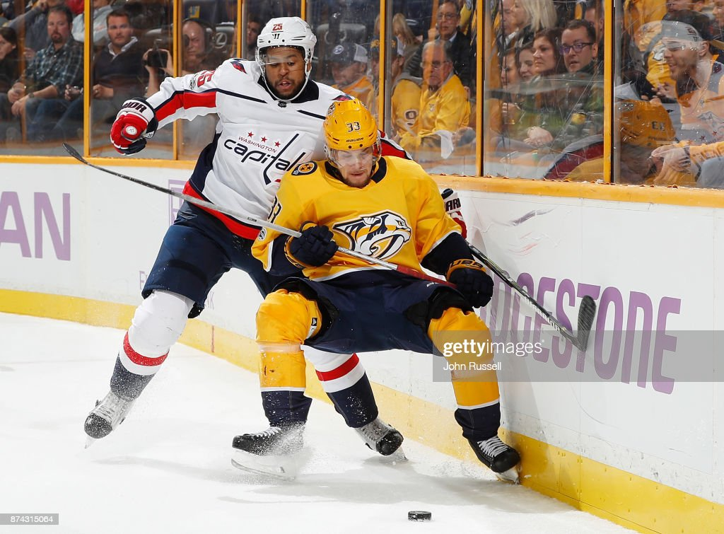 Viktor Arvidsson #33 of the Nashville Predators battles behind the net for the puck against Devante Smith-Pelly #25 of the Washington Capitals during an NHL game at Bridgestone Arena on November 14, 2017 in Nashville, Tennessee.