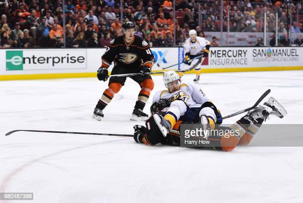 Viktor Arvidsson of the Nashville Predators falls over Brandon Montour of the Anaheim Ducks during the first overtime period of Game One of the...