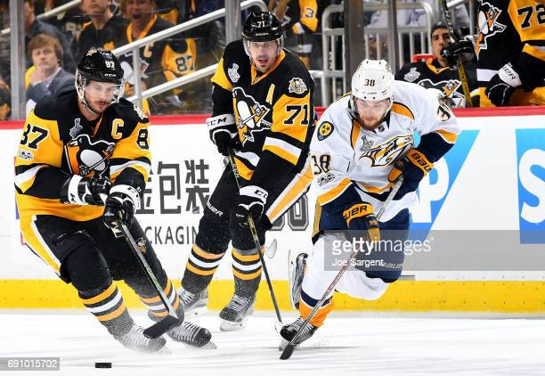 Viktor Arvidsson of the Nashville Predators handles the puck in front of Sidney Crosby of the Pittsburgh Penguins and Evgeni Malkin of the Pittsburgh...
