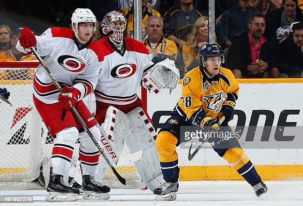 Viktor Arvidsson of the Nashville Predators skates against Noah Hanifin an dCam Ward of the Carolina Hurricanes during an NHL game at Bridgestone...