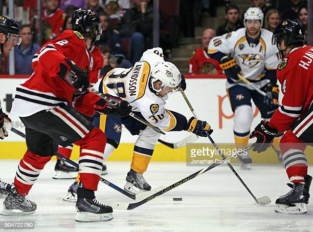 Viktor Arvidsson of the Nashville Predators tries to control the puck between Duncan Keith and Niklas Hjalmarsson of the Chicago Blackhawks at the...