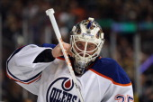 Viktor Fasth of the Edmonton Oilers adjusts his mask against the Anaheim Ducks at Honda Center on April 2 2014 in Anaheim California