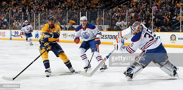 Viktor Fasth of the Edmonton Oilers clears the puck against Eric Nystrom of the Nashville Predators at Bridgestone Arena on November 27 2014 in...