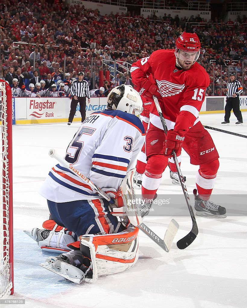 Viktor Fasth of the Edmonton Oilers makes a save as Riley Sheahan of the Detroit Red Wings looks for a rebound during an NHL game on March 14 2014 at...