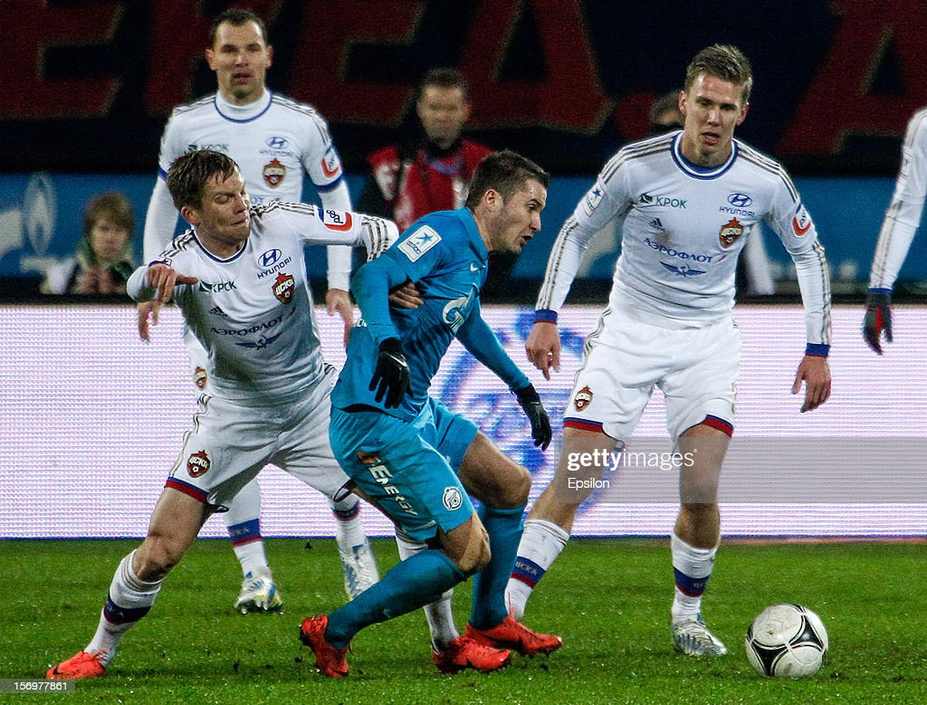 Viktor Fayzulin (R) of FC Zenit St. Petersburg in action against Aleksandrs Cauna of PFC CSKA Moscow (L) and Pontus Wernbloom of PFC CSKA Moscow during the Russian Football League Championship match between FC Zenit St. Petersburg and PFC CSKA Moscow at the Petrovsky Stadium on November 26, 2012 in St. Petersburg, Russia.